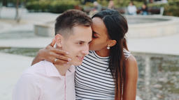 Pretty black lady whispering something in boyfriend's ear and then showing keep GIF