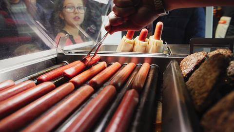 girl looks at seller taking sausage for hotdog slow motion GIF