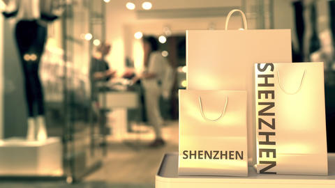 Shopping bags with SHENZHEN text against blurred store. Chinese retail related Footage