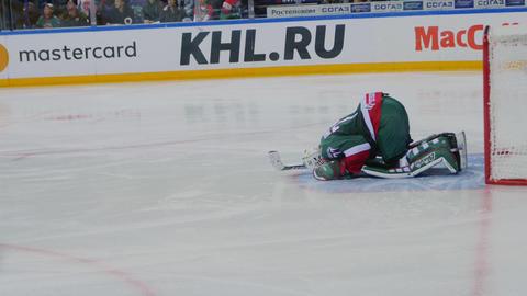goalkeeper in uniform near gate at hockey match on arena GIF