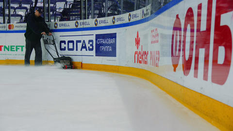 man in uniform cleans arena before hokey game with machine ビデオ