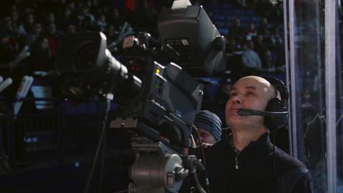 bald cameraman shoots hockey match on large modern stadium GIF