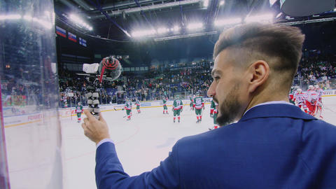 journalist with microphone at hockey game on large ice arena 動画素材, ムービー映像素材