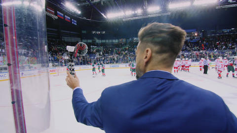 journalist with microphone at hockey game on large ice arena ビデオ