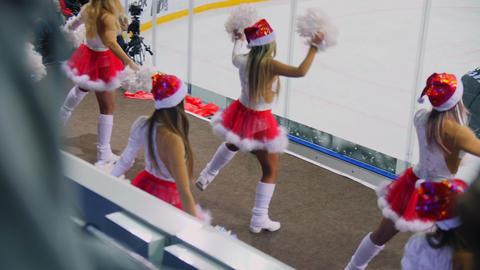 cheerleaders in Santa caps dance near ice rink backside view GIF