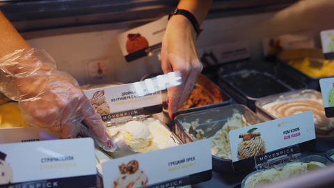 woman takes ice-cream scoop in fastfood cafe close view Archivo