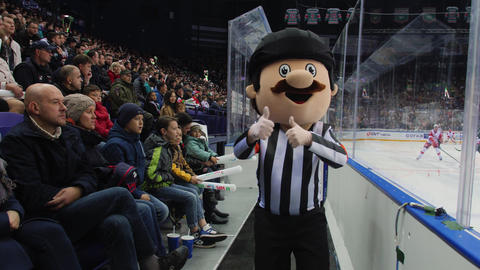mascot person in hockey judge suit runs by modern ice arena GIF