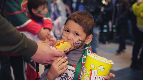 little boy bites tasty hotdog holding popcorn slow motion GIF