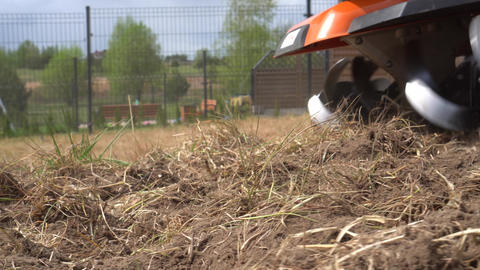 Cultivator blades plowing soil with grass. Gimbal motion movement closeup shot GIF