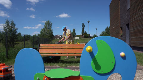 Young man mows lawn near children colorful playground. Gimbal movement Live Action