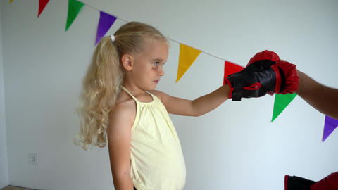 Father put boxing gloves on child hands. Daddy and daughter learn self defense Live Action