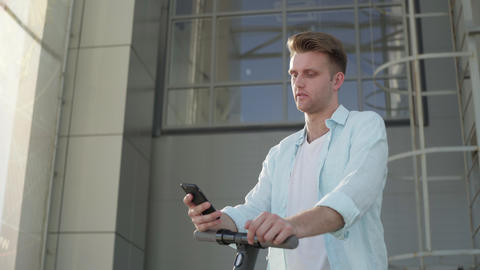 A guy with electric scooter using his phone outdoors Live Action