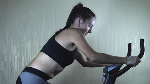 Woman training on exercise bike at home GIF