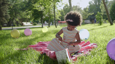 Happy african kid girl drawing in the park with multicolored balloons on GIF