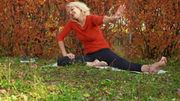 Smiling mature woman stretching on mat in autumn park ビデオ