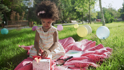 Happy Little african-american girl play with present box on her birthday GIF