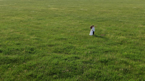 A couple of lovers stands in the middle of a field with green grass. They laugh GIF