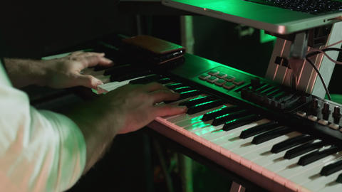 Male hands play music on the piano at a concert. Playing the electronic piano GIF
