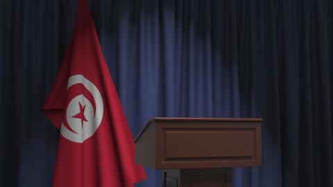 Flag of Tunisia and speaker podium tribune. Political event or statement related Live Action