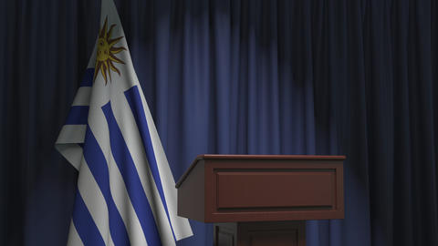 Flag of Uruguay and speaker podium tribune. Political event or statement related Live Action