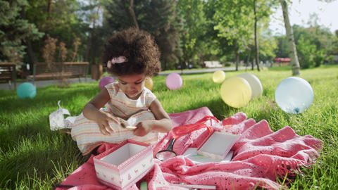 Little african kid girl is playing in the park with multicolored balloons on GIF