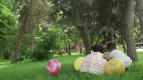 Little african-american girl and boy play with multicolored balloons in the park GIF