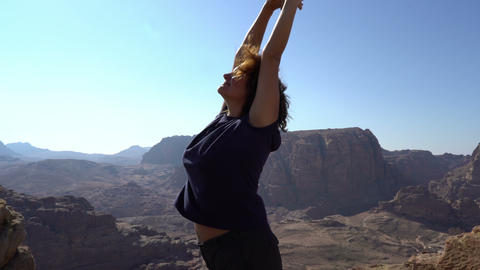 Woman standing at top of mountains with wonderful nature view and stretching ビデオ