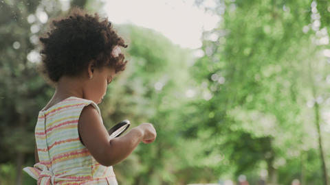 Little african-american girl is playing with magnifier in the park GIF