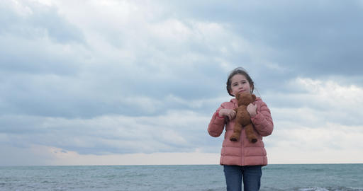 Little girl hugs a teddy bear on the beach ビデオ
