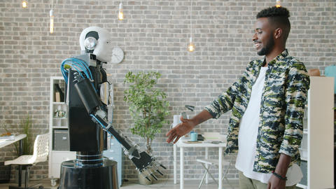 Side view of happy Afro-American businessman shaking hand to smart cyborg ビデオ