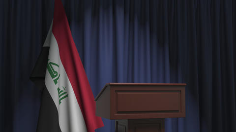 Flag of Iraq and speaker podium tribune. Political event or statement related Live Action