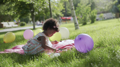 Little african-american girl is sitting in the park and drawing GIF