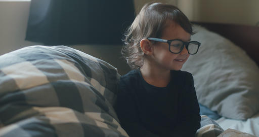 Funny little baby girl wearing parents glasses on bed ビデオ