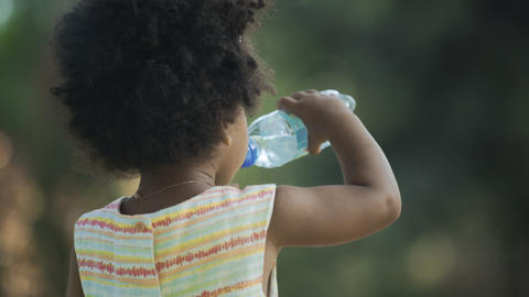 Back view of little african-american girl drinking water GIF