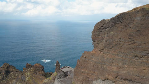 Aerial view of steep cliffs over Atlantic Ocean. Flight over people admiring GIF