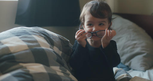 Funny little baby girl wearing parents glasses on bed GIF
