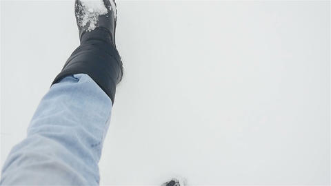 A man walks in the snow. Close-up of walking legs. Winter season. Slow motion ビデオ