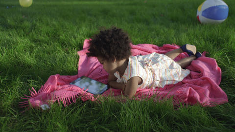 Little african-american girl lies in the park on the bedspread and watches GIF