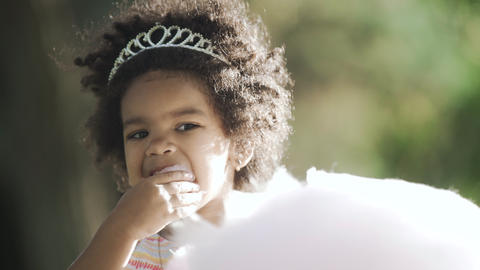 Close up of african-american girl with diadem on head eating cotton candy GIF