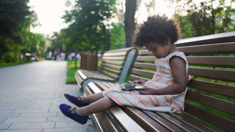 Little african-american girl is sitting on bench in the park and watching GIF
