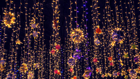 Beautiful colorfull holidays decorations sway on wind against night sky Live Action