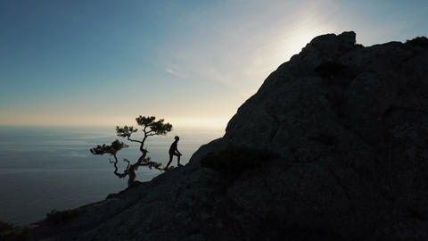 Epic Aerial view of a silhouette of a young woman climbing to the top of a GIF