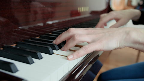 A lesson in a music school, learning to play the piano. Female hands play the Live Action