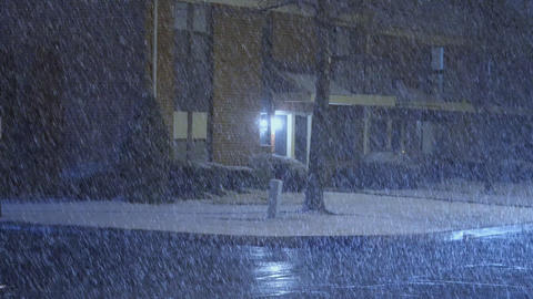 Cars driving slowly, snow covered street in a residential area at night ビデオ