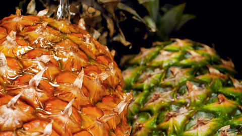 Closeup slow motion video of water slowly pouring on fresh ripe pineapples Archivo