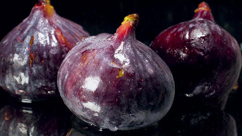 Closeup slow motion video of water droplets falling on fresh ripe figs against Archivo