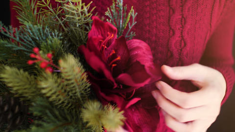 Female wear red sweater holding christmas flower bouquet Live Action