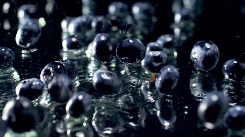 Slow motion macro footage of blueberries falling on wet black surface. Perfect Archivo