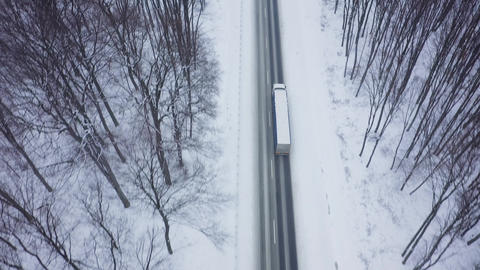 Aerial view of truck driving on the road surrounded by winter forest in snowfall Footage