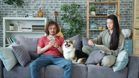 Man using smartphone while woman storking dog and reading book in apartment Archivo